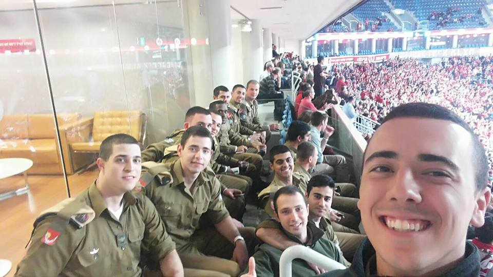 A group of smiling IDF soldiers enjoy a night out at the HaPoel Jerusalem basketball game.