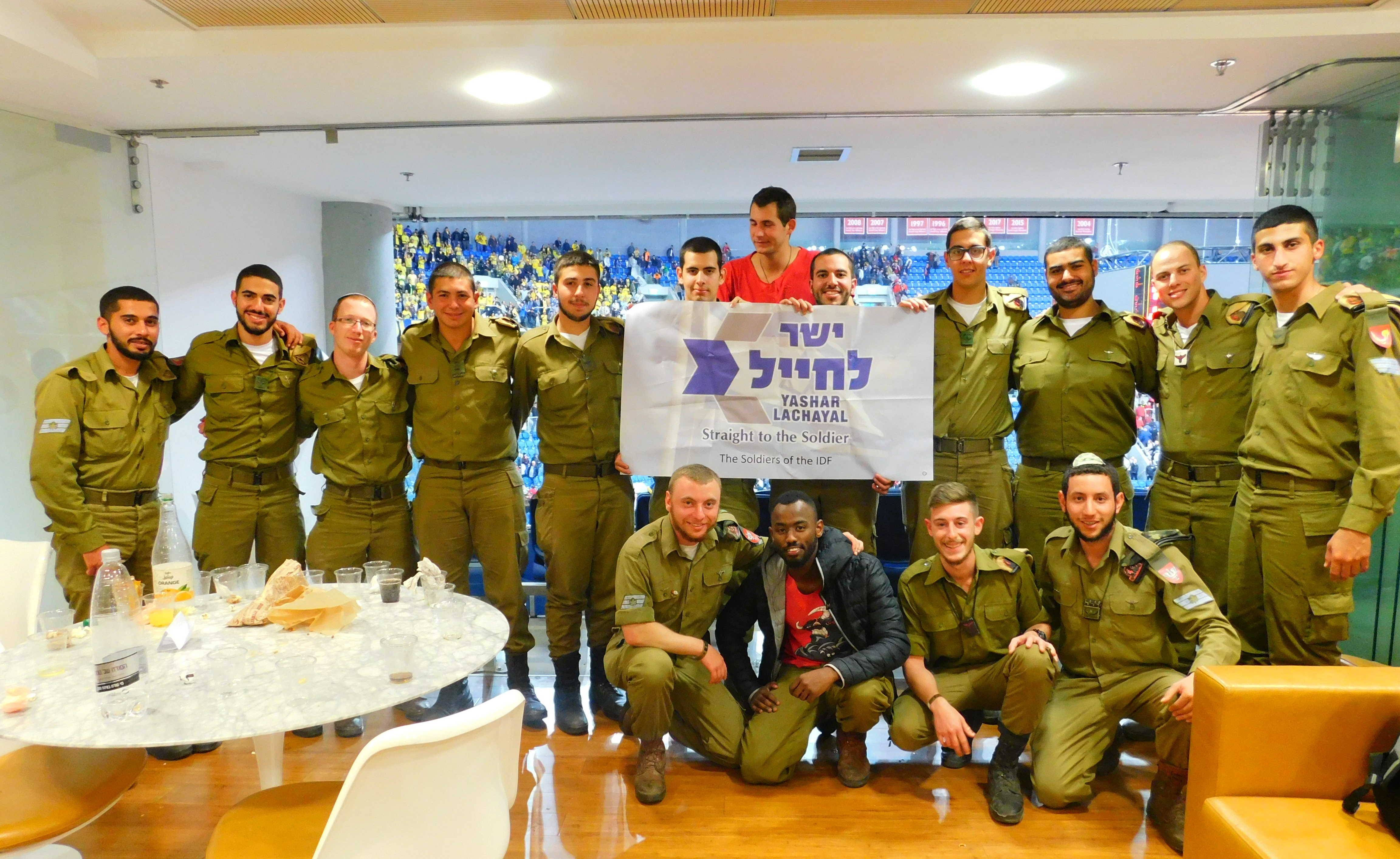 A group of IDF soldiers pose in the VIP box at a sport stadium.