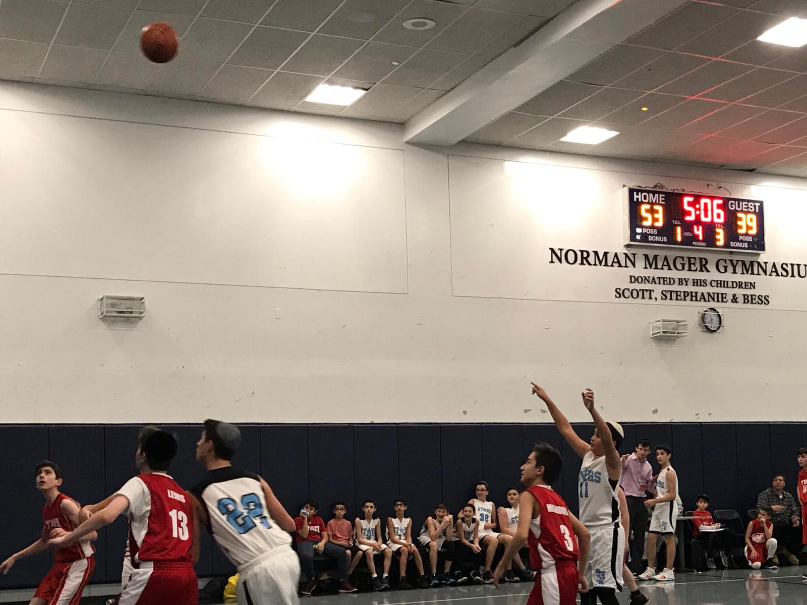 Yeshiva middle school students play basketball.