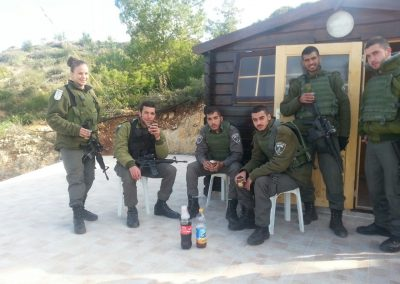 A group of soldiers sitting and enjoying a cool beverage outside a wooden Warm Corner in Ateret