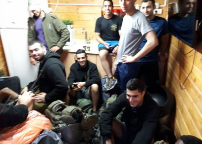 Group of soldiers hanging out inside a wooden Warm Corner.