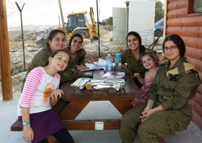IDF soldiers enjoy a meal with children from Nokdim at Yashar LaChayal's Warm Corner.